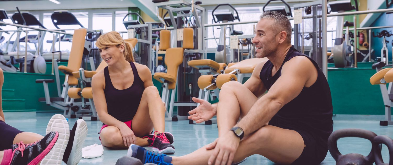 A group of fitness people sitting in a gym discussing their exercises