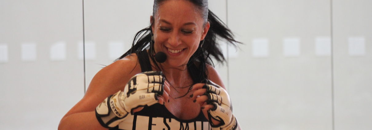 A group exercise instructor in a body conditioning class, smiling at the front