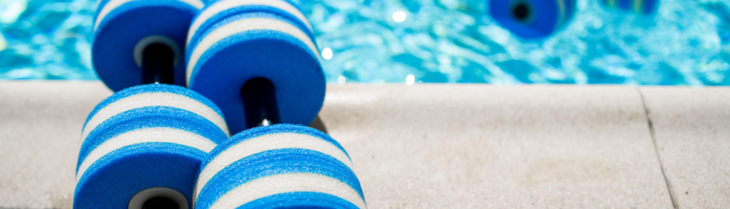Hand buoys for water workouts by the edge of a swimming pool
