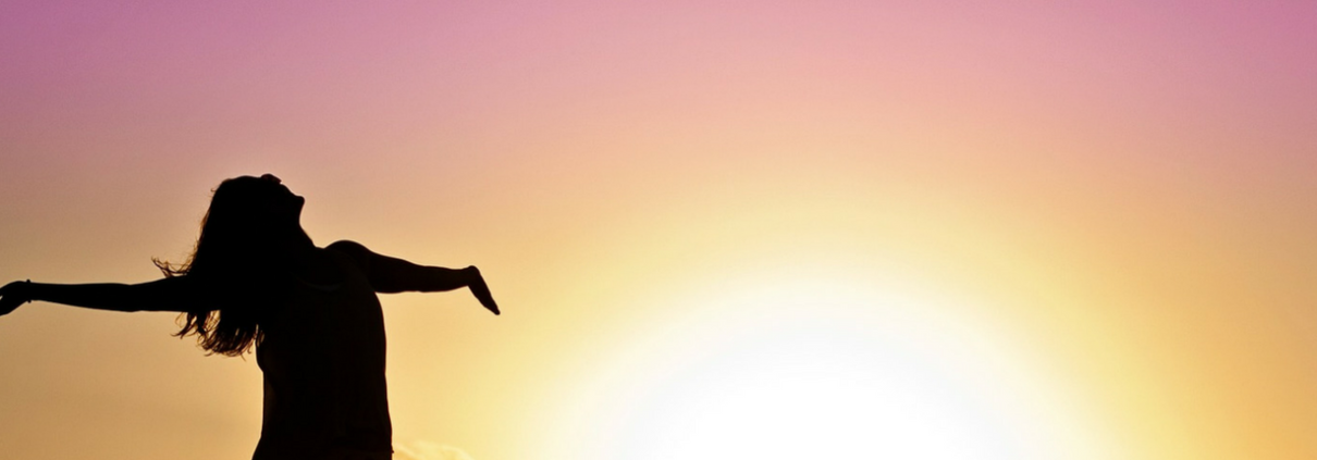 Woman with outstretched arms enjoying the sunset