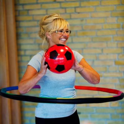 A woman holding a football and enjoying a Powerhoop class