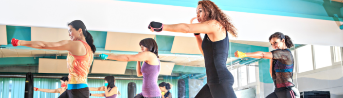 Women doing a combat based group exercise class