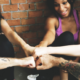A group of exercise instructors fist-bumping after a class