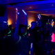 People in a darkened room doing Clubbercise with glow sticks