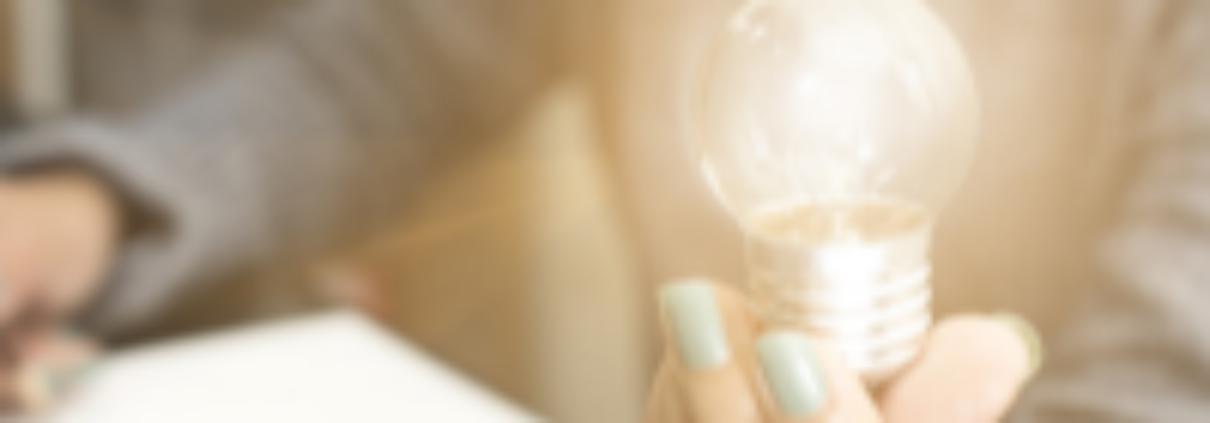 A woman holding a light bulb having an idea