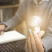 A woman holding a light bulb having an idea